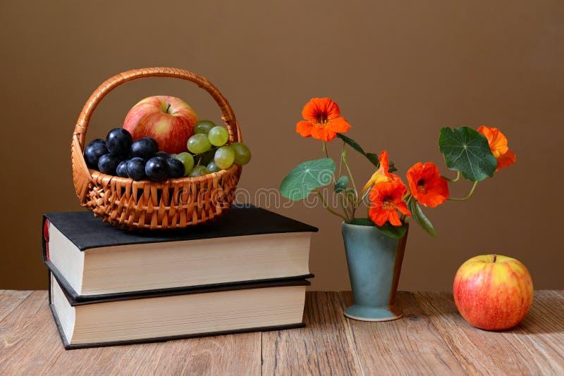 在的新鲜水果篮子柳条、书和花 免版税库存图片