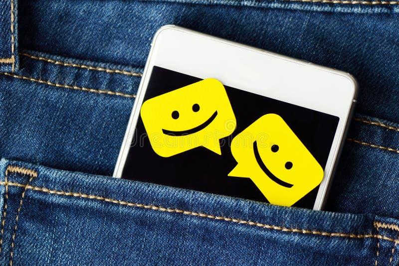 在的智能手机牛仔裤装在口袋里与闲谈消息泡影 免版税库存图片