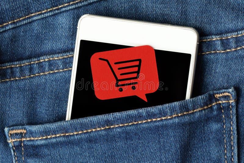 在的智能手机牛仔裤装在口袋里和与购物的消息泡影 库存图片