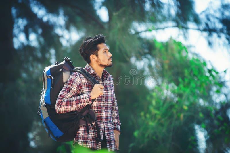 在的步行期间疲乏的远足者人放松与一个大背包 免版税库存图片
