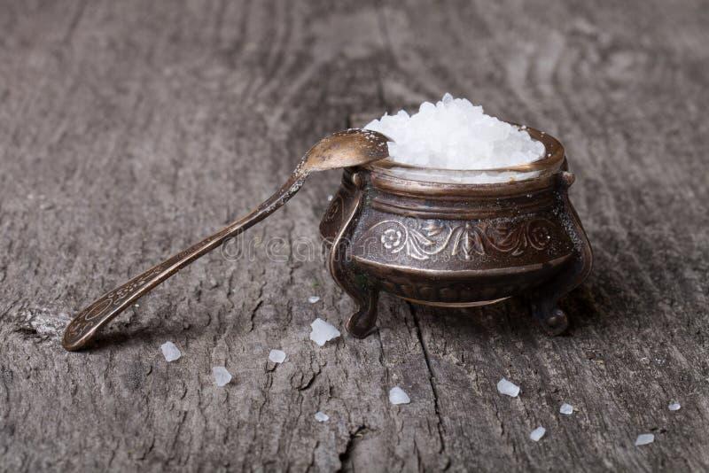 在的海盐老器物和一把小匙子在一张木桌上 免版税库存照片