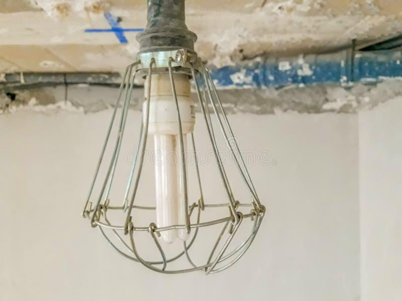 在的电灯泡与围拢它的金属保护一起使用和建筑的底部 图库摄影