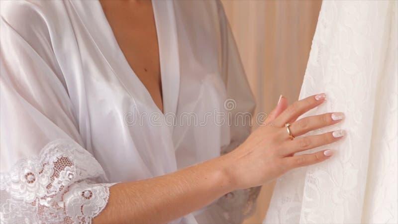 在的白色婚礼礼服肩膀,在仪式前 接近穿戴婚姻 美好的婚礼五颜六色的花束和 免版税库存照片
