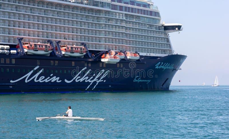 在的里雅斯特停泊的游轮附近的划船者 免版税库存照片