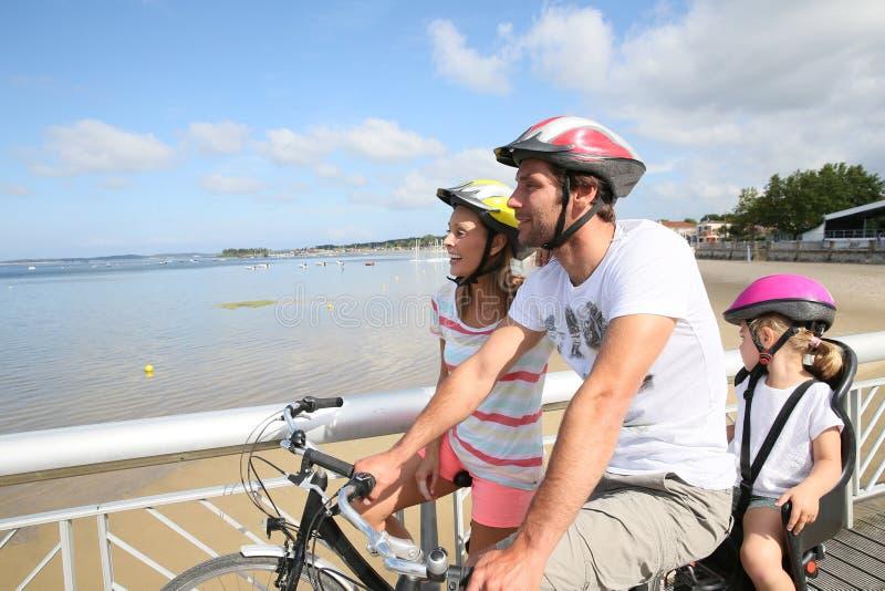 在的年轻家庭由海边的骑自行车的天 图库摄影