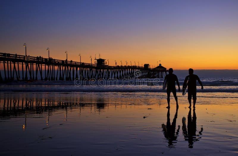 在皇家海滩码头日落的冲浪者剪影 库存照片