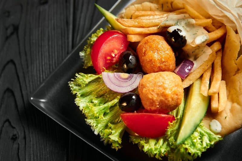 在皮塔饼的电罗经与沙拉三明治、橄榄和希脂乳 传统希腊烹调盘 在黑木背景的健康午餐 免版税库存图片