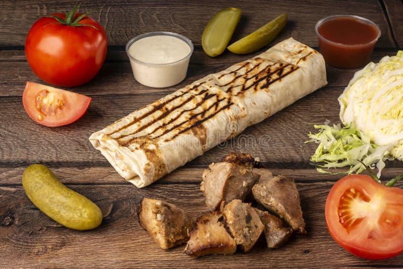 在皮塔饼面包的外带的便当与新鲜蔬菜、猪肉和调味汁 图库摄影