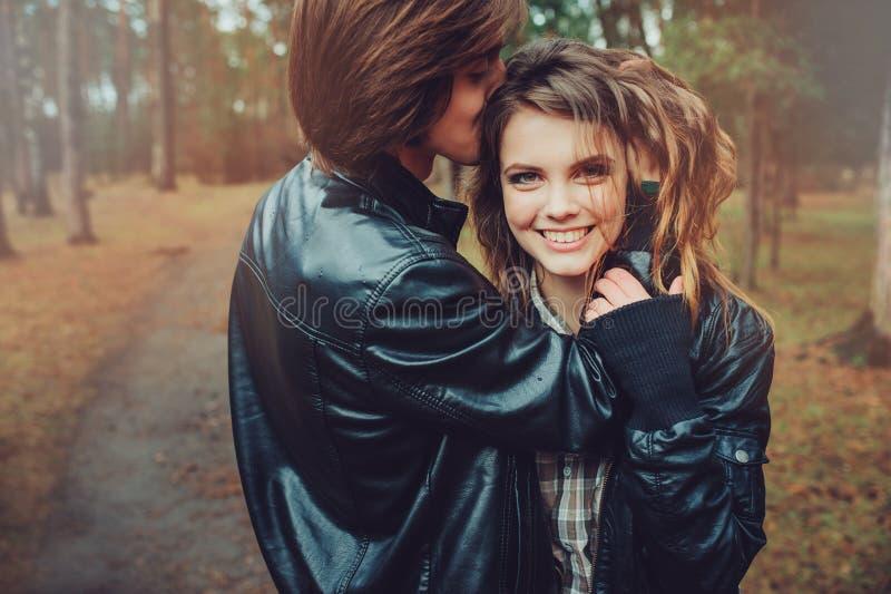 在皮夹克的年轻愉快的爱恋的夫妇在森林里拥抱室外在舒适步行 免版税库存照片