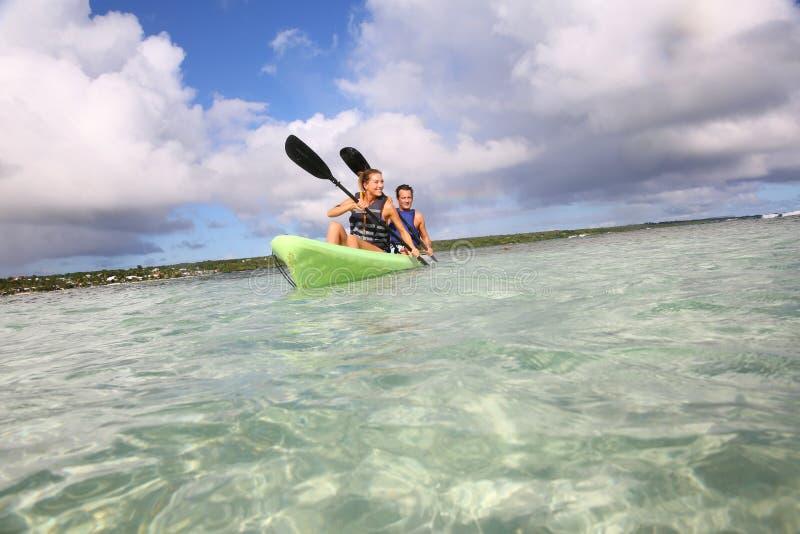 在皮船的夫妇划船在海边 库存图片