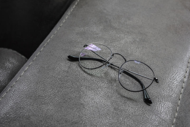在皮革沙发的角落的一块玻璃 免版税图库摄影