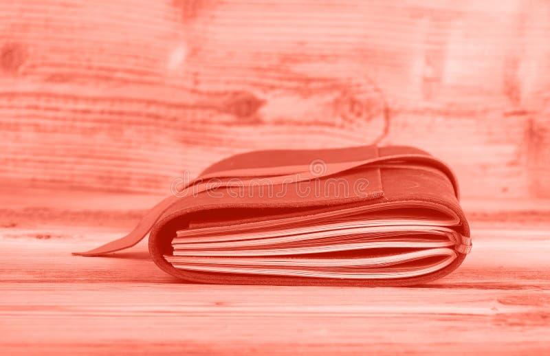 在皮革盖子的桃红色被定调子的笔记本在桌上 库存照片