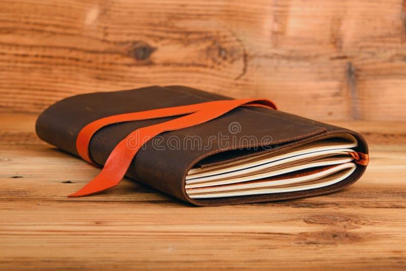 在皮革盖子的笔记本在木桌上 库存图片