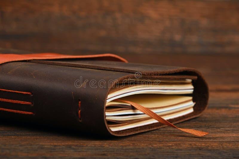 在皮革盖子的笔记本在木桌上 图库摄影