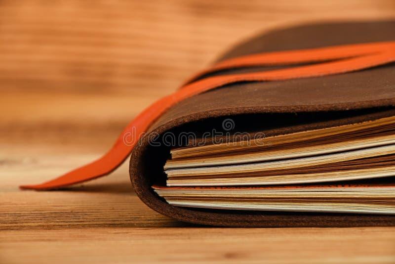 在皮革盖子的笔记本在木桌上 免版税库存图片