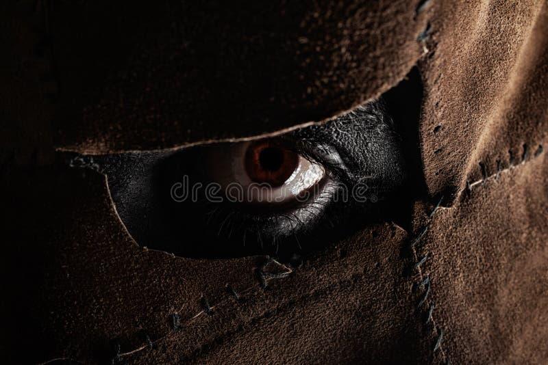 在皮革面具的邪恶的凶手眼睛 库存照片
