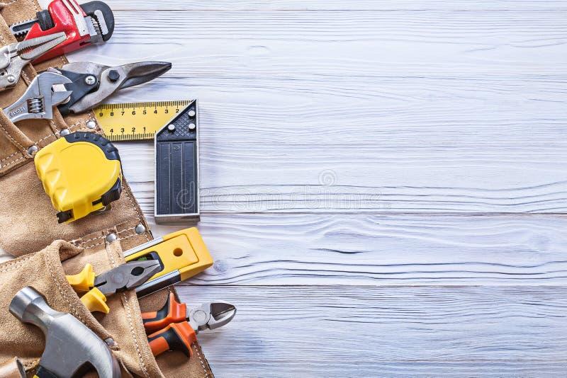 在皮革toolbelt的建筑凿出的装饰在木板拷贝sp 免版税库存图片