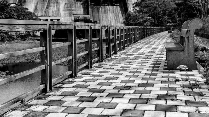在监督水坝和河的步行道路的长凳 免版税库存照片
