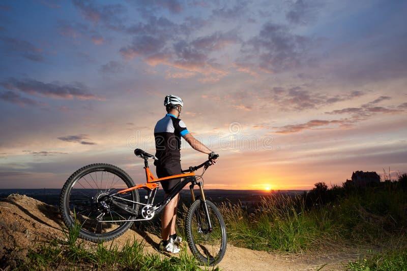 在盔甲和体育的后面看法骑自行车者男性给日落背景的基于穿衣  免版税图库摄影