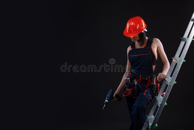 在盔甲的俏丽的妇女建造者与操练她的站立在梯子和看在黑背景的手 库存照片