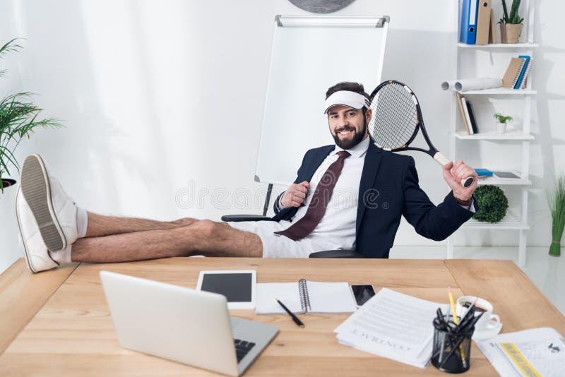 在盖帽的年轻商人有休息在工作场所的网球拍的 免版税库存照片