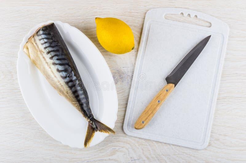 在盘、柠檬和刀子的熏制的鲭鱼在切板 免版税库存照片