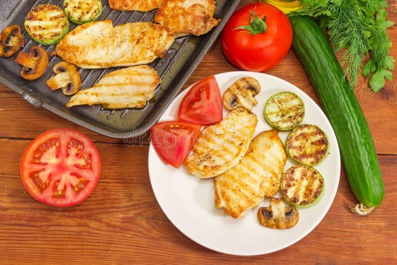 在盘和格栅平底锅,菜,绿色的烤鸡肉 库存图片