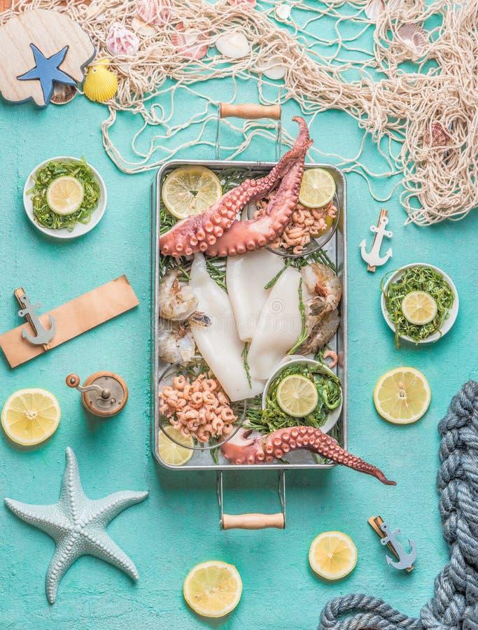 在盘子的各种各样的海鲜在与渔网、海草和成份,顶视图的浅兰的背景 免版税图库摄影