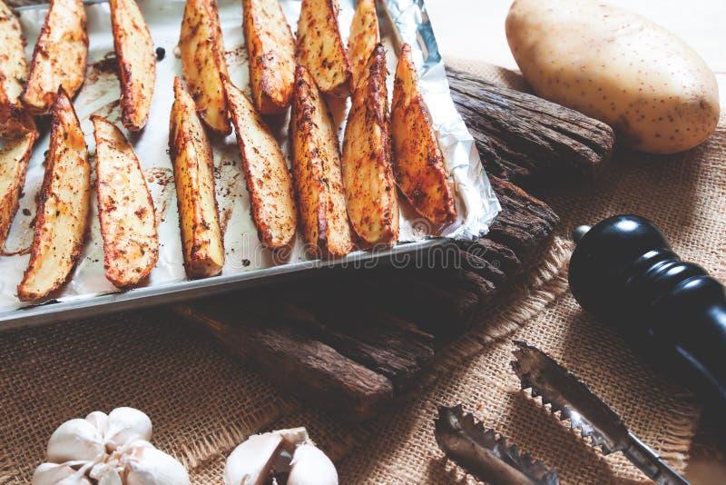 在盘子的被烘烤的土豆用黑胡椒和大蒜在土气木板 素食主义者食物或快餐 免版税库存照片