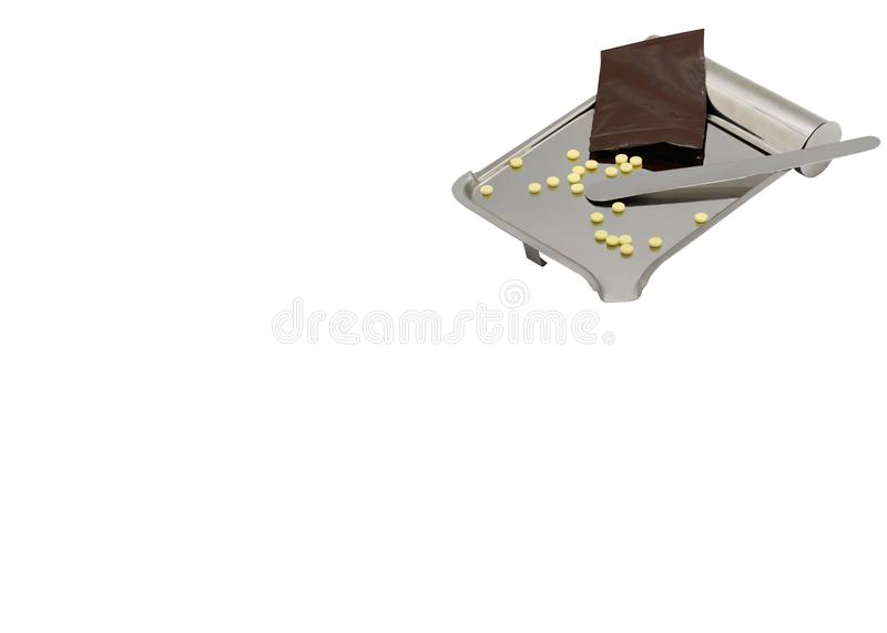 在盘子的黄色药片从医学用拉锁拉上在被隔绝的白色bac的袋子 库存图片