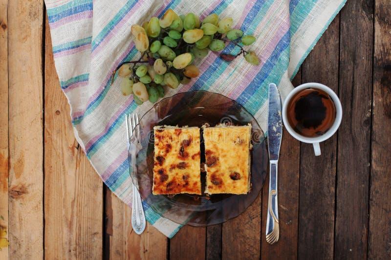 在盘的乳酪砂锅用在一把木背景、刀子和叉子,果子,早晨,可口早餐的绿色葡萄 免版税库存照片
