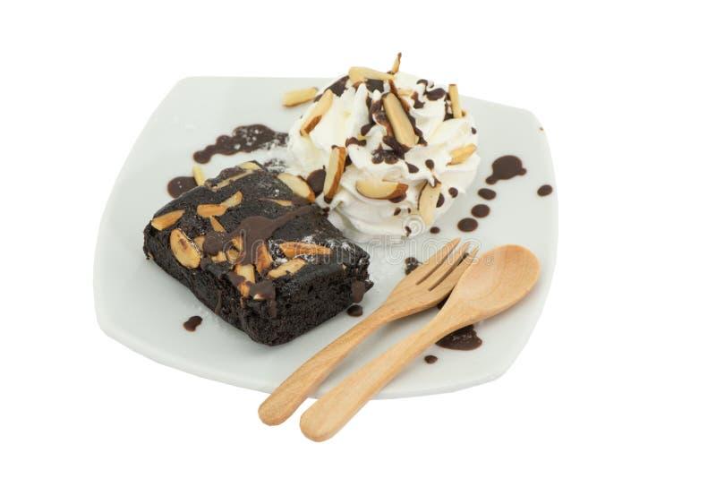 在盘的果仁巧克力蛋糕在白色背景 免版税库存图片