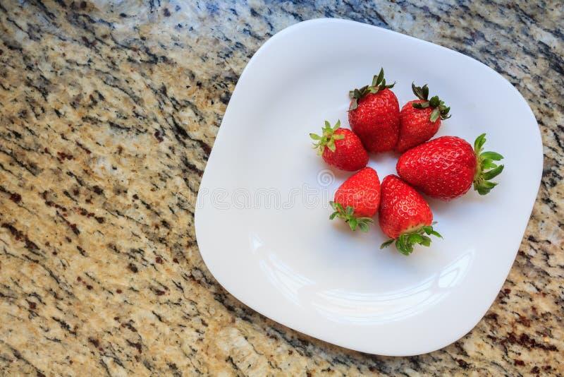 在盘的水多的新鲜的草莓白色,在大理石桌背景,可口点心 免版税图库摄影
