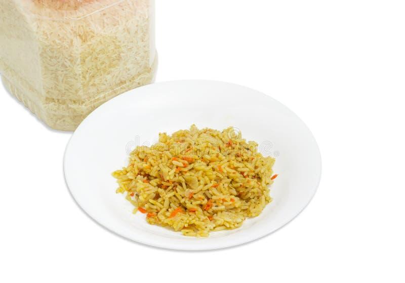 在盘的煮熟的米和在塑胶容器的未煮过的米 免版税图库摄影