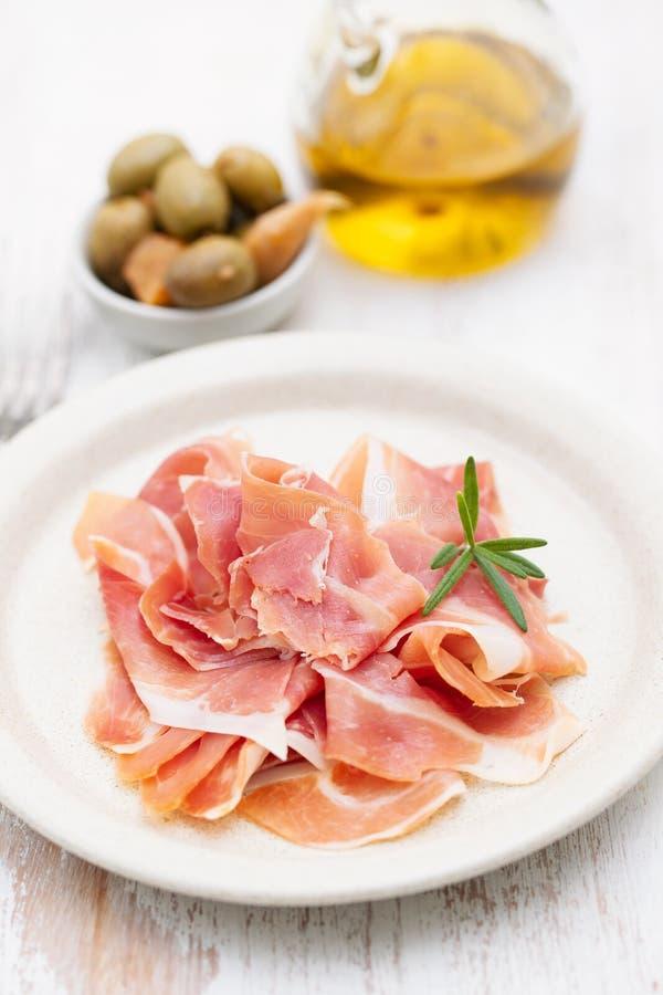 在盘的熏火腿与橄榄油和橄榄 库存照片