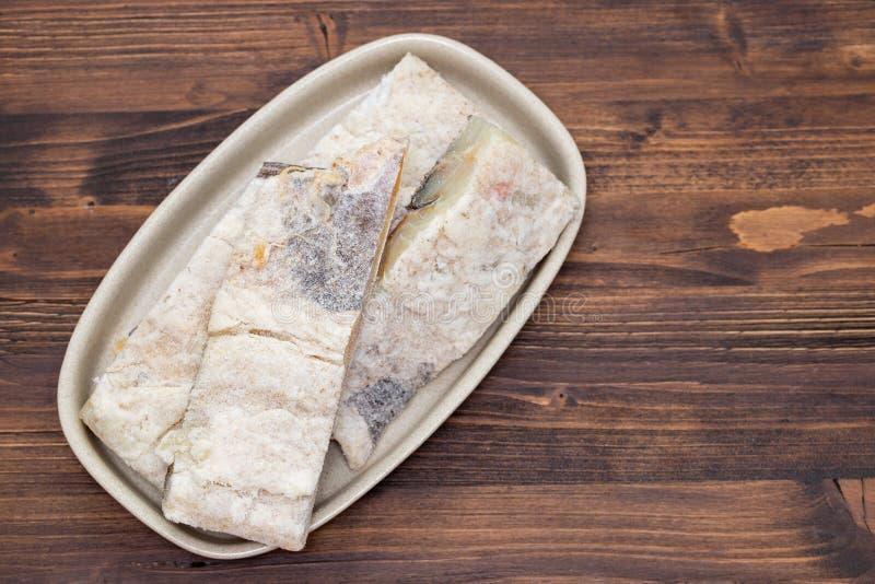 在盘的盐味的干燥鳕鱼在棕色背景 免版税库存图片