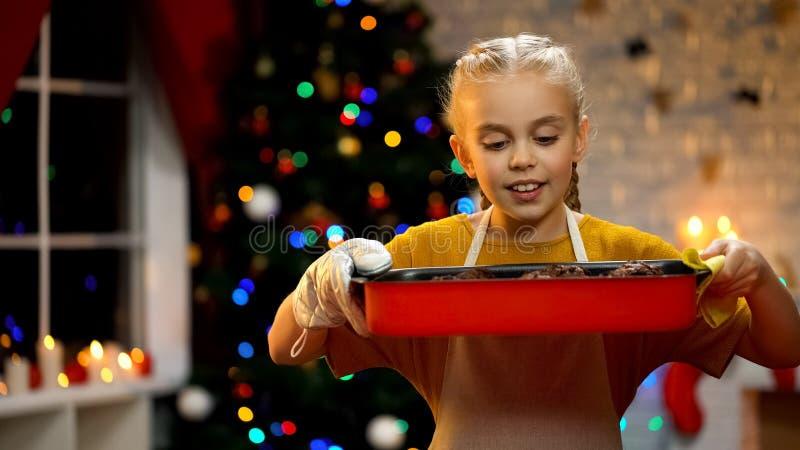 在盘的逗人喜爱的女孩嗅巧克力碎片松饼,传统圣诞节准备 库存照片