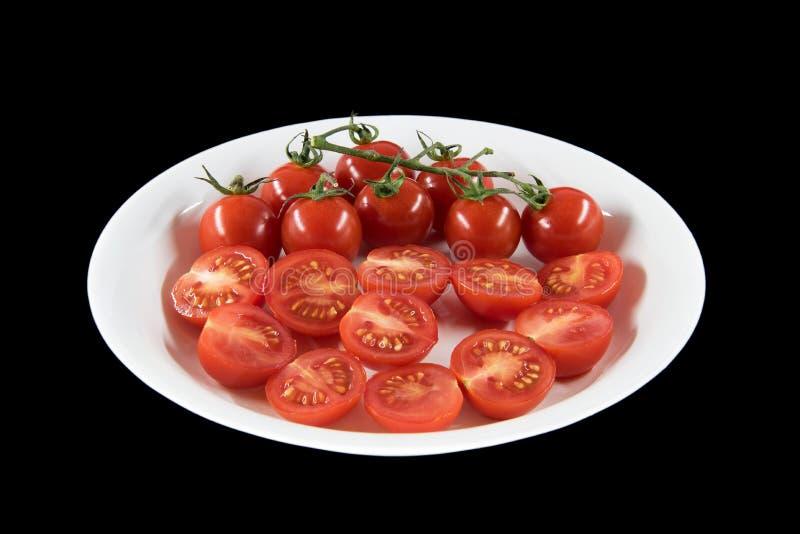 在盘的cuted蕃茄有黑背景 免版税库存照片