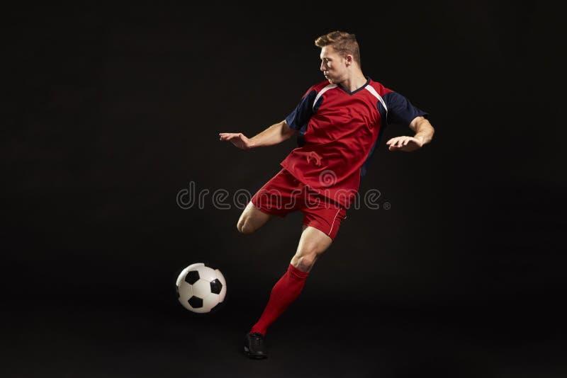 在目标的专业足球运动员射击在演播室 免版税图库摄影