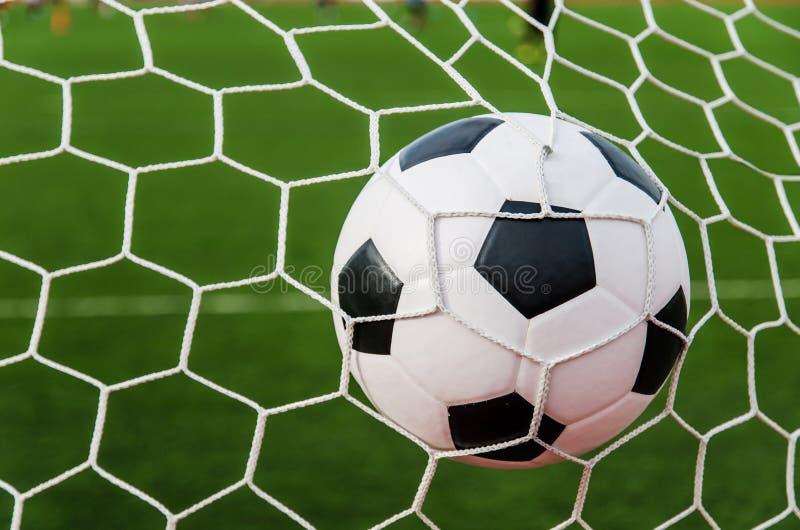 在目标网的足球橄榄球与绿草领域 图库摄影