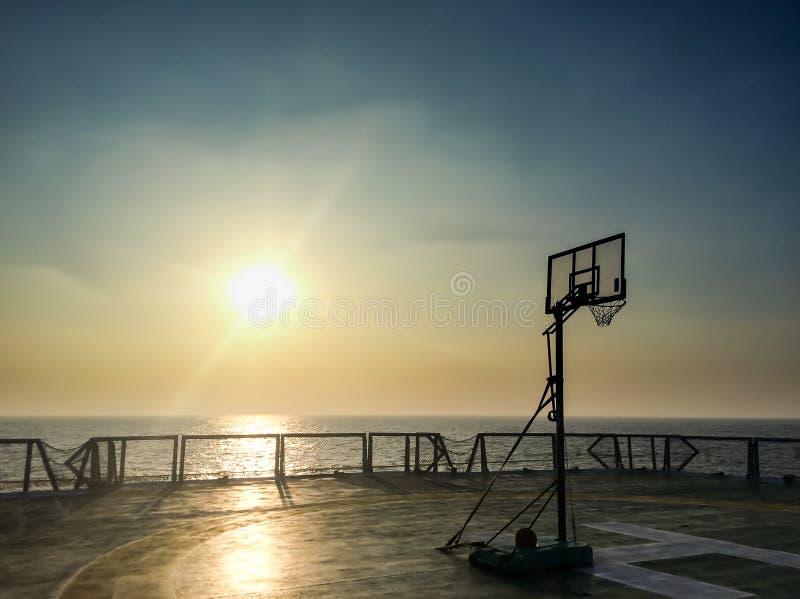 在直升机坪的篮球场蓝球板在日落期间的地震船船在油和煤气调查的安达曼海与天空 库存照片