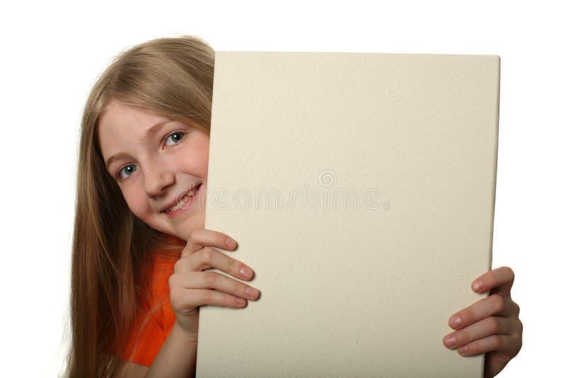在相当偷看的广告牌空白女孩 库存照片