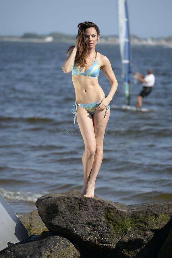 在相当摆在海滩的蓝色比基尼泳装的有吸引力的模型晃动 图库摄影