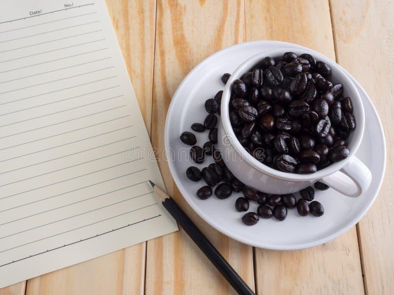 在相当白色杯子和备忘录的烤咖啡豆在木桌上 库存图片