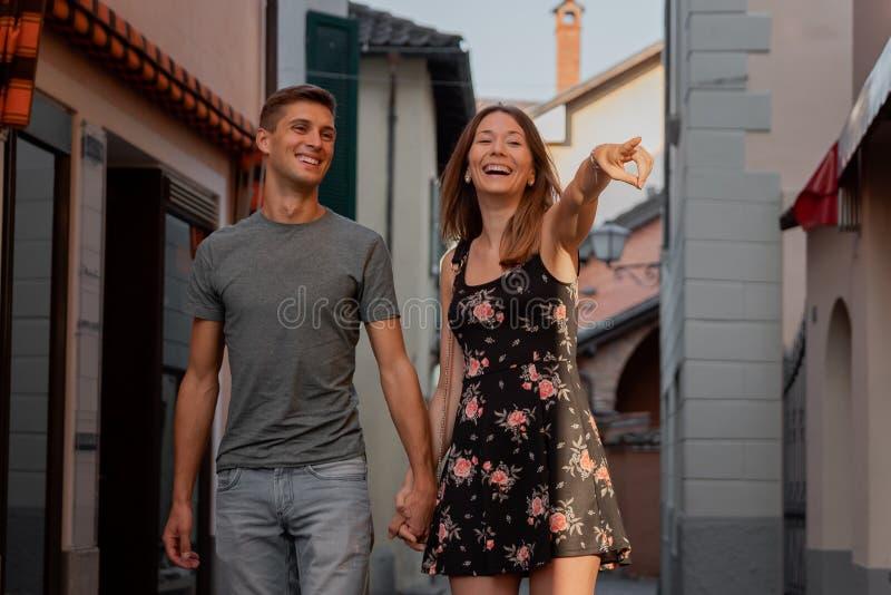 在看在一个胡同的爱的年轻夫妇商店窗口在ascona在日落期间 库存图片