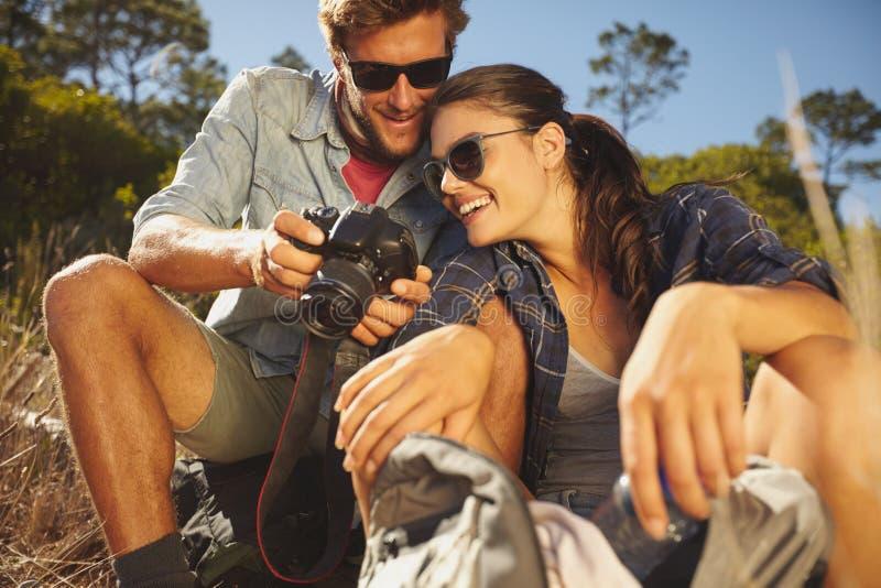 在看在数字照相机的远足的微笑的夫妇图片 免版税库存图片