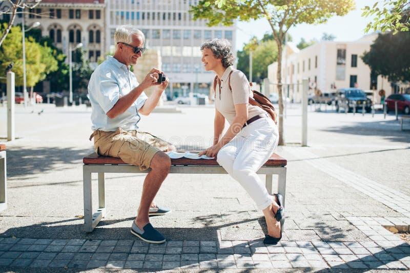 在看在照相机的长凳的资深旅游开会图片 免版税库存图片