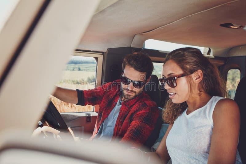 在看地图的汽车的年轻夫妇为方向 免版税库存图片