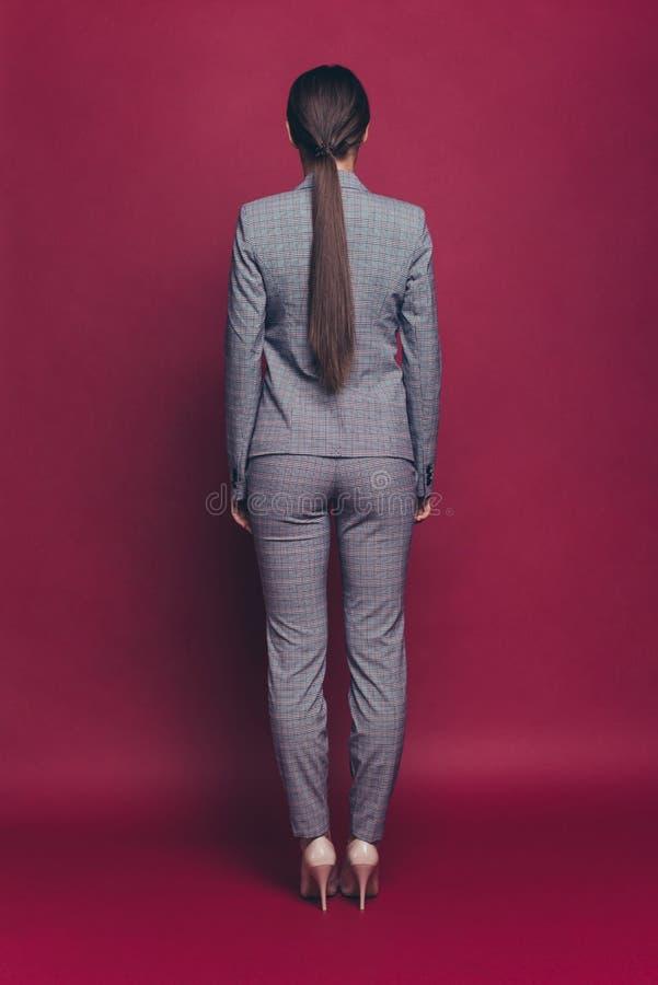 在看法全长身体尺寸画象的垂直的后方后面她后她好相当可爱夫人佩带灰色 免版税库存照片