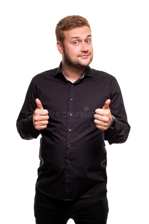 在看照相机和显示拇指的白色背景的黑衬衣身分打扮的年轻可爱的人的图象 库存照片